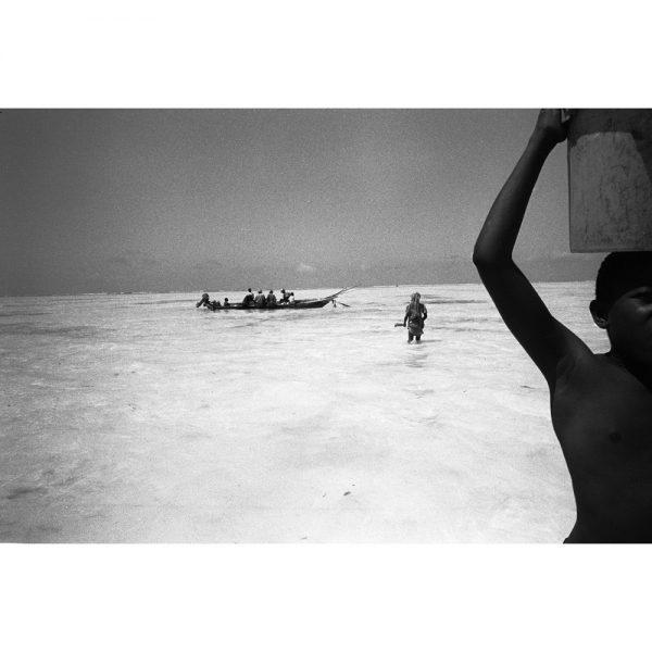 漁から帰って来た漁師達が海岸に着く。バケツ一杯の魚を頭に乗せて船を降りる少年。ザンジバル、タンザニア、2008年。©Toru Morimoto/Akashi Photos