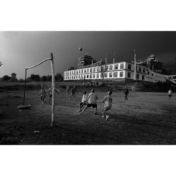 チベットから亡命してきた僧侶達が彼らのチベット仏教寺院の裏でサッカーを楽しむ。ビール、インド、2006年。©Toru Morimoto/Akashi Photos