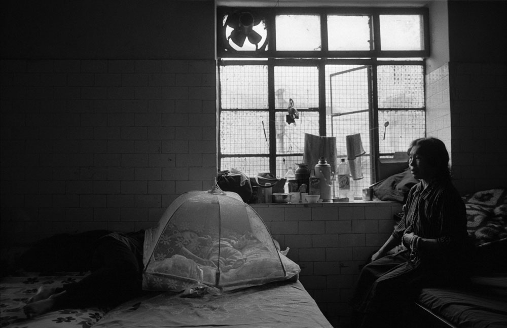 An exiled Tibetan mother with her baby on the bed in a refugee center in Dharamsala, India.