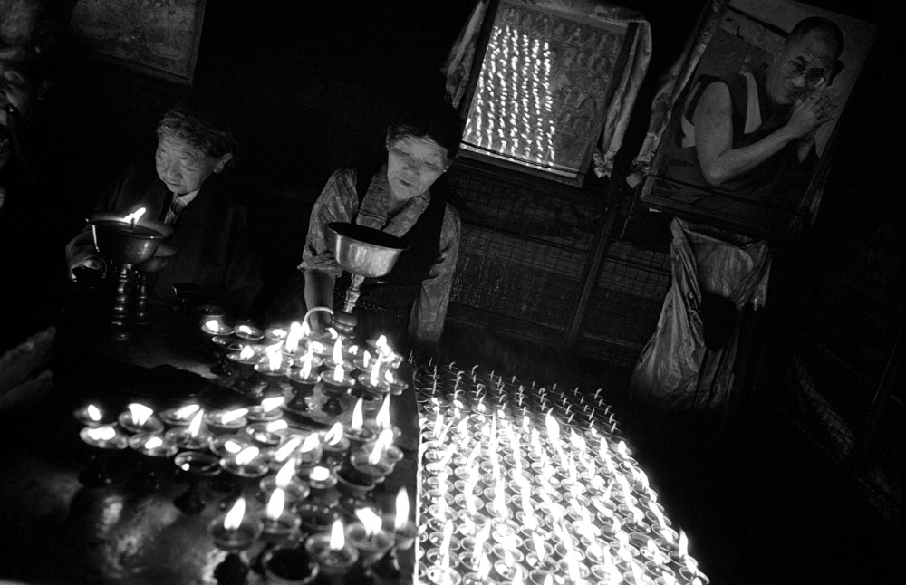 Tibetans pilgrims light up candles in the Bodhnath stupa with the portrait of Dalai Lama, Nepal