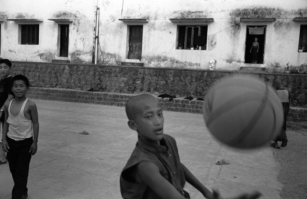 Tibetan monks play basketball beside the Tibetan monastery in Bir, India
