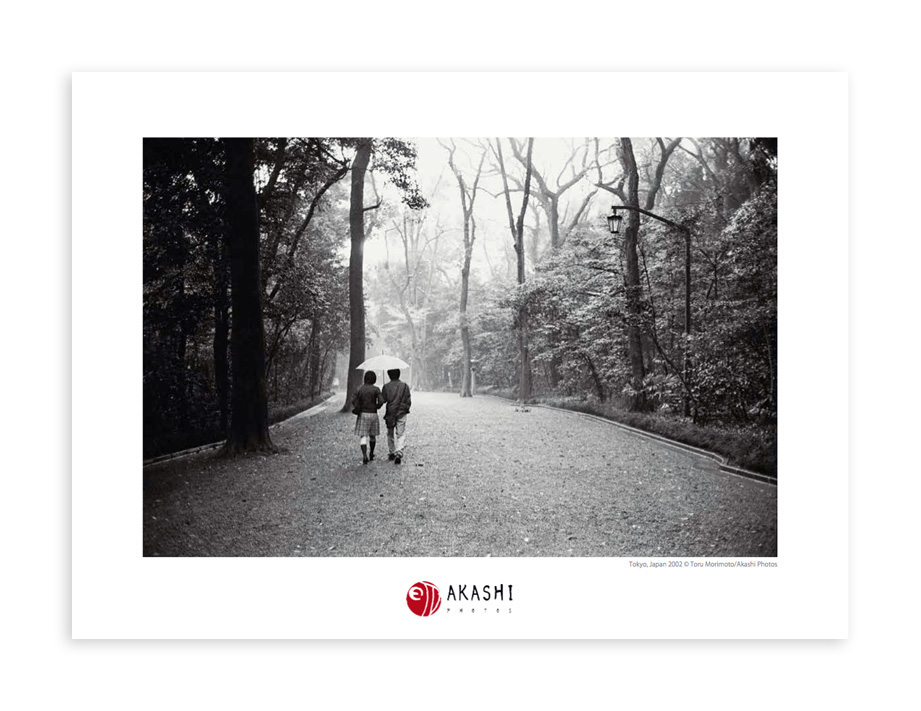 A Japanese couple walks under an umbrella on a path in Meiji Jingu Shrine.