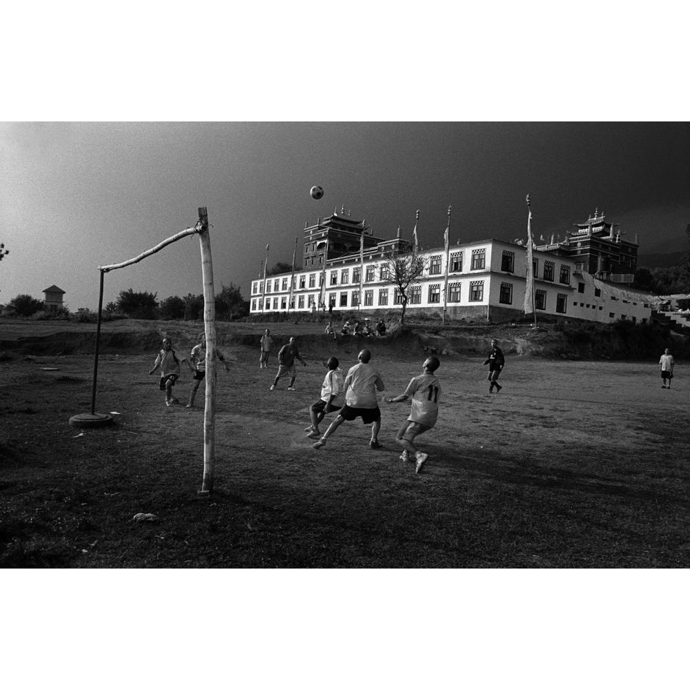 Exiled Tibetan Monks play soccer behind their monastery. Bir, India