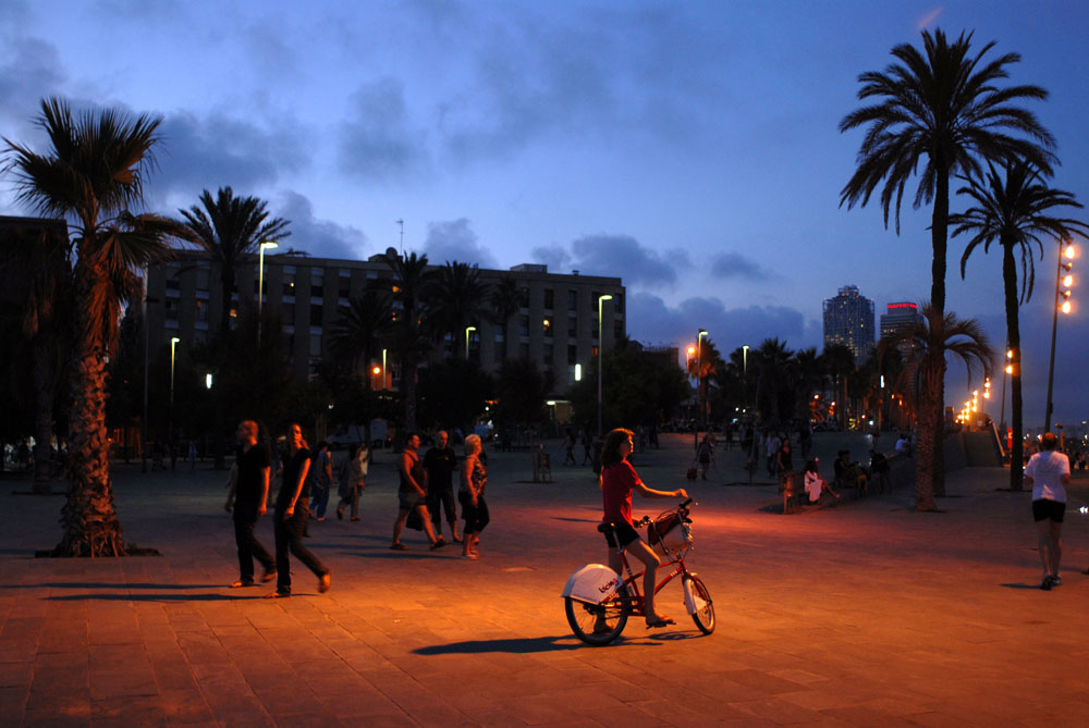 A girl on Bicing, Barcelona's pulic bicycle, in Barceloneta Beach