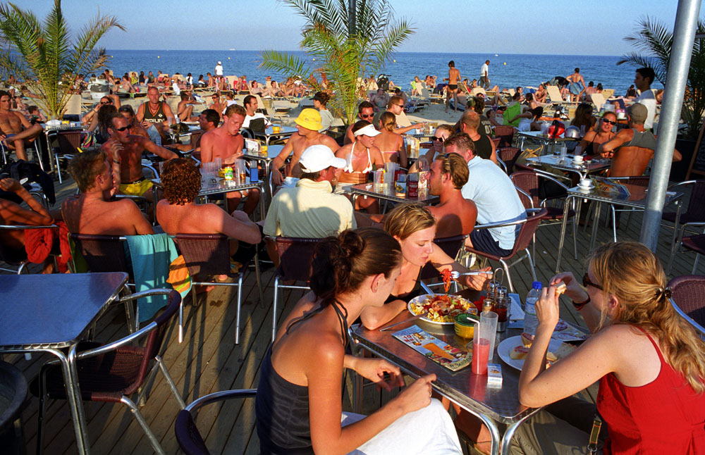 Tourists at the bar on the Barceloneta beach in Barcelona, Spain.