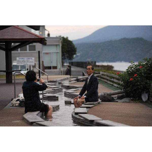 A couple takes pictures with Sakurajima behind while they put their feet in Ashiyu. Kagoshima, Kyushu, Japan