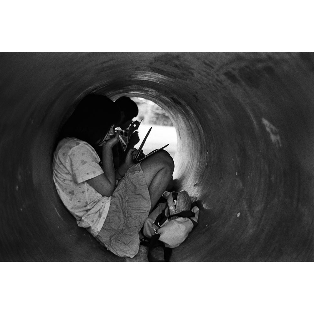 Japanese young girls put make-up on in a concrete pipe in a park. Matsumoto, Nagano.