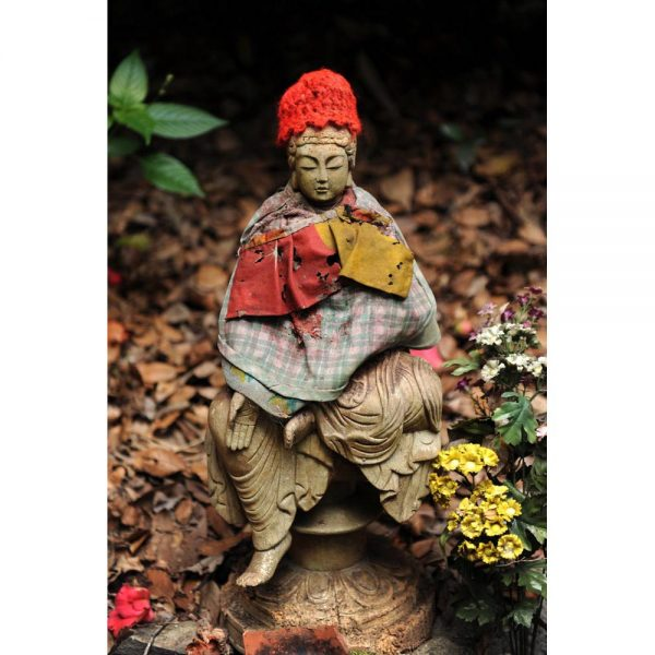 Jizo, protector of women, children, and travelers, sits on the path on the way to a temple on the route of Shikoku Henro.